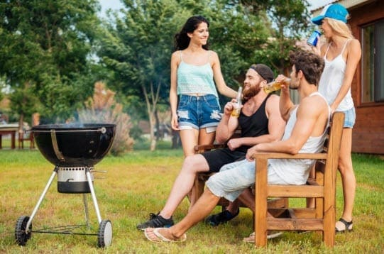 two couples grilling outside