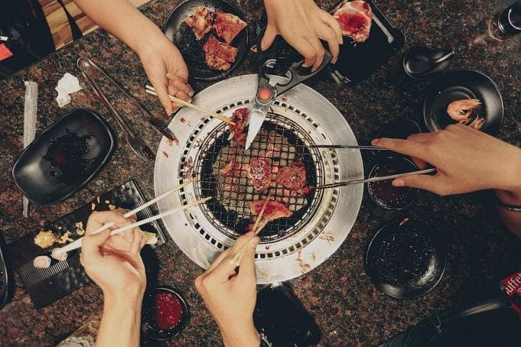 people eating out of  a tabletop grill