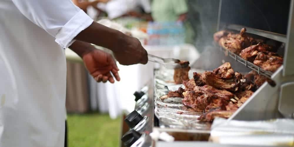 an image of a man cooking chicken in a gas grill